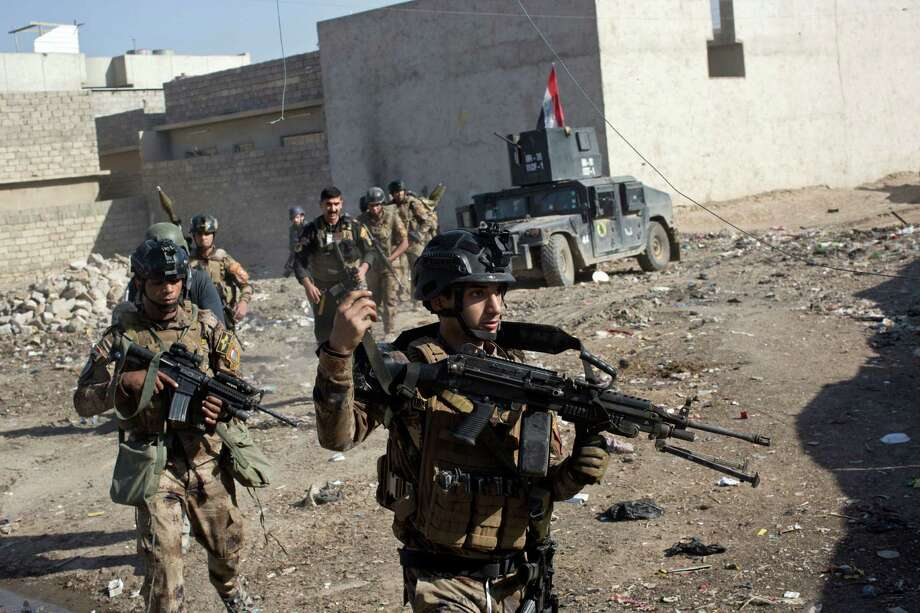 Iraqi special forces soldiers move in formation in an alley on the outskirts of Mosul, Iraq, Friday, Nov. 4, 2016. Heavy fighting erupted in the eastern neighborhoods of Mosul on Friday as Iraqi special forces launched an assault deeper into the urban areas of the city and swung round to attack Islamic State militants from a second entry point, to the northeast. (AP Photo/Marko Drobnjakovic) ORG XMIT: XMD105 Photo: Marko Drobnjakovic / Copyright 2016 The Associated Press. All rights reserved.