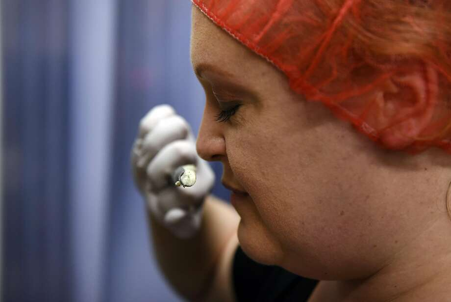 Owner Seana Doughty takes a sniff of a sample plug from a wheel of Buff Blue cheese. Photo: Michael Short, Special To The Chronicle