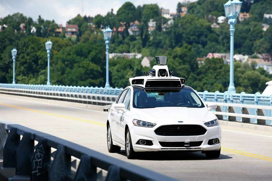 Uber employees test a self-driving car in Pittsburgh this summer. Will taxi drivers eventually lose their jobs?  Photo: Jared Wickerham, FRE / FR171279