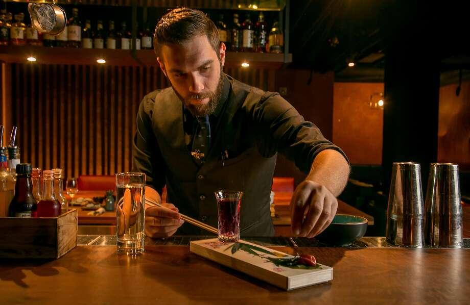 Bartender Alex Riddle makes the Sakura Festival cocktail. Photo: John Storey