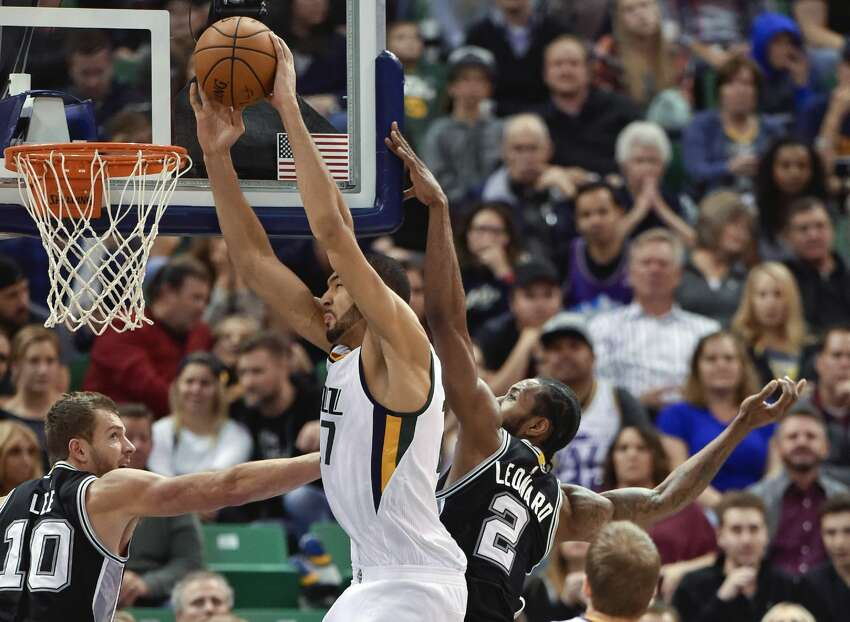 SALT LAKE CITY, UT - NOVEMBER 04: Rudy Gobert #27 of the Utah Jazz goes to the basket between the defense of David Lee #10 and Kawhi Leonard #2 of the San Antonio Spurs in the second half of the Spurs 100-86 win at Vivint Smart Home Arena on November 4, 2016 in Salt Lake City, Utah. NOTE TO USER: User expressly acknowledges and agrees that, by downloading and or using this photograph, User is consenting to the terms and conditions of the Getty Images License Agreement. (Photo by Gene Sweeney Jr/Getty Images)