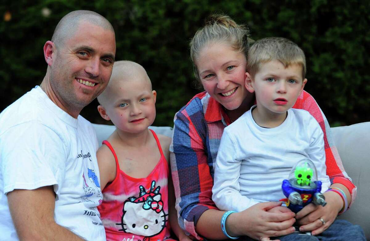 Cancer survivor Mia McCaffrey, 6, poses with her dad Jim, mom Marian and brother James, 4, at their home on Cottage Street in Trumbull on Wednesday. Mia has been featured in a viral music video called