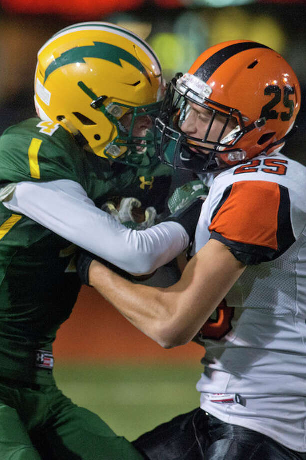 BRITTNEY LOHMILLER | blohmiller@mdn.net Dow High's Brendan Kuch, left, fights to maintain possession after catching a pass from Ben Zeitler while Fenton High's Alex Marshal works to strip the ball from him in the first half of the Division 2 playoff game Friday night.
