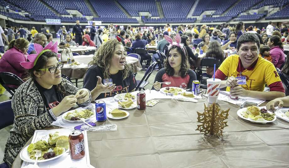 From left: Frankie Garcia, Ale Iglesias, Casey Seca and Luis Garcia share a conversation as they enjoy a turkey meal Saturday morning during the 2015 H-E-B Feast of Sharing at the Laredo Energy Arena. Photo: Victor Strife /Laredo Morning Times / Laredo Morning Times