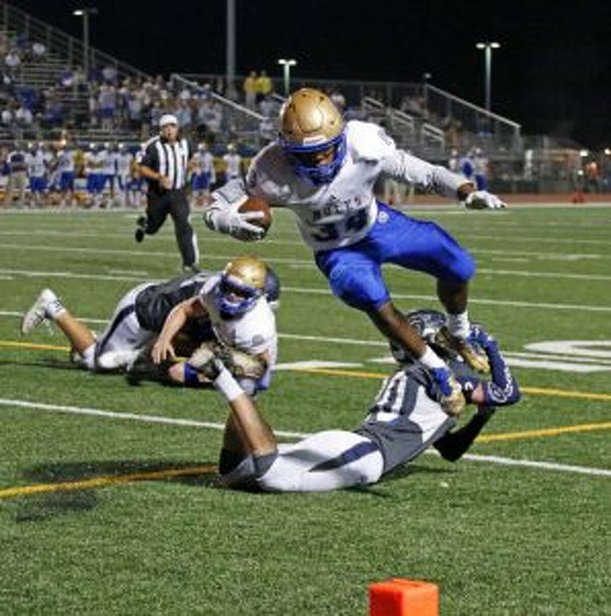 Alamo Heights Deryl Reynolds hurdles over Boerne Champion's Kaden Beavers for a TD from the District 26-5A high school football game between Alamo Heights and Boerne Champion on Friday, October 28, 2016. Alamo Heights will soon replace their turf on their field with the same turf used by the Dallas Cowboys and Houston Texans. (Staff photo)
