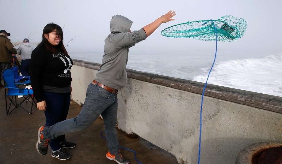 Jared Tadio throws a crab net from the municipal pier into the surf in Pacifica, Calif. on Saturday, Nov. 5, 2016 for the first day of the recreational Dungeness crab season. Despite all of the enthusiasm, veteran crabbers say conditions were less than ideal as heavy surf continually pounded the pier. Photo: Paul Chinn, The Chronicle