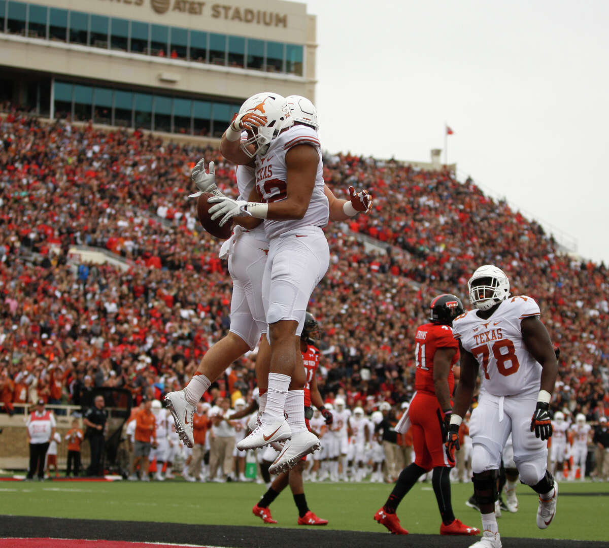 Texas' Andrew Beck celebrates with tight end Caleb Bluiett after Bluiett scored in the second quarter of an NCAA college football game against Texas Tech, Saturday, Nov. 5, 2016, in Lubbock, Texas. (Mark Rogers/Lubbock Avalanche-Journal via AP)