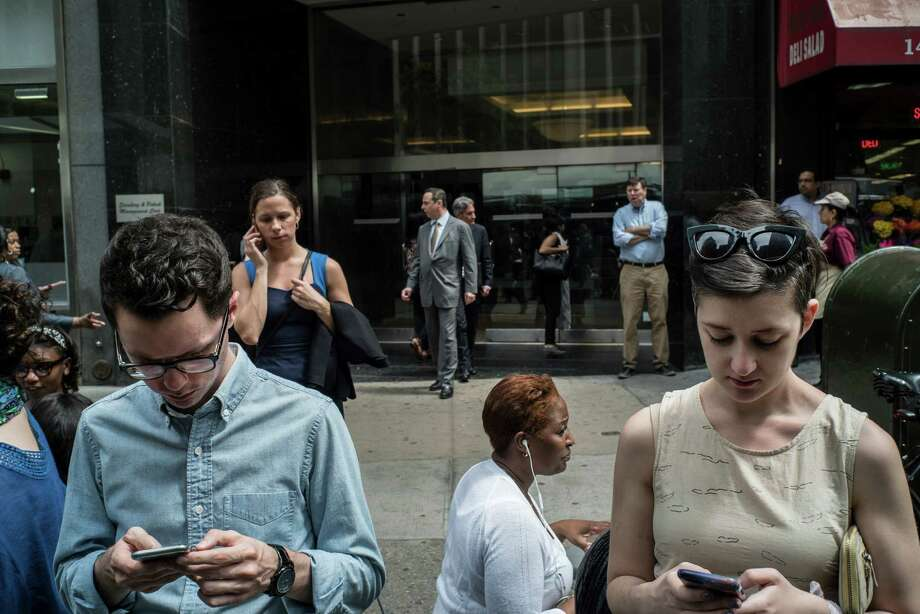 FILE -- People on their phones in New York, May 12, 2015. Tailored advertising is a generally accepted part of the internet experience — consumers see it daily on their mobile devices, and now AT&T and Time Warner are pointing to targeted advertising on TV as a major benefit of their proposed $85 billion merger. (Todd Heisler/The New York Times) Photo: TODD HEISLER, STF / NYTNS