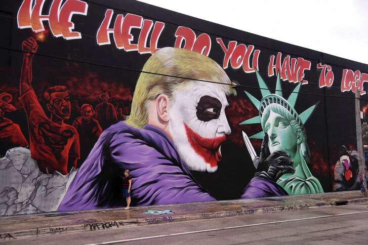 TOPSHOT - A woman poses for a photo in front of a Donald Trump mural covering a building in the Wynwood neighbourhood of Miami, Florida, on October 27, 2016.  The Anti-Trump, batman themed mural was created by the artists of the Bushwick Collective ahead of the US presidential election.  / AFP PHOTO / RHONA WISE / RESTRICTED TO EDITORIAL USE - MANDATORY MENTION OF THE ARTIST UPON PUBLICATION - TO ILLUSTRATE THE EVENT AS SPECIFIED IN THE CAPTIONRHONA WISE/AFP/Getty Images