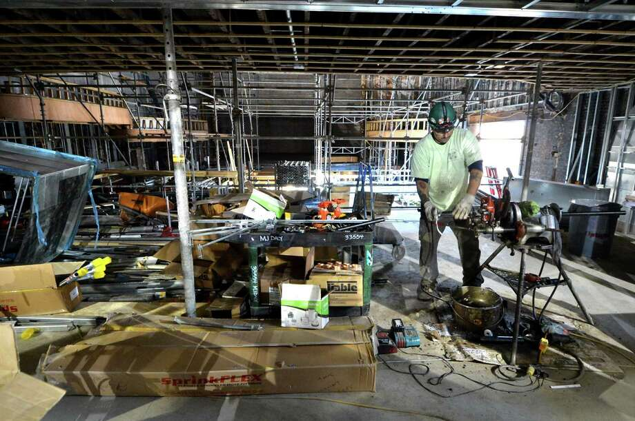 Workers with M.J. Daly construct the fire supression system inside the Wall Street Theater on Wednesday November 2, 2016. The century-old theater may open as early next year as a venue for live shows, interactive entertainment and digital productions in Norwalk Conn. Photo: Alex Von Kleydorff / Hearst Connecticut Media / Connecticut Post