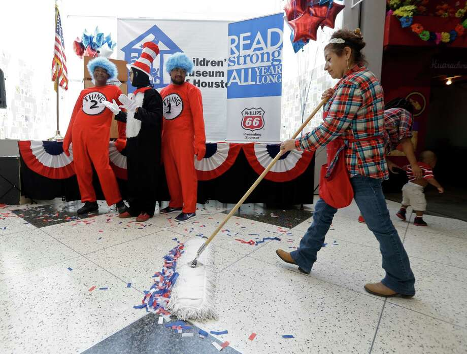 Maria Torres, right, sweeps up confetti  as Thing 2, Kevonte Miller, left, The Cat In Hat, Nicholas Cuellar, and Thing 1, Winstone Saniel, hang out after celebration of the Cat winning during The Cat In The Hat Runs for President event at the Children's Museum of Houston 1500 Binz, Saturday, Nov. 5, 2016, in Houston. Children cast votes for either The Cat In The Hat or Thing1 and Thing2. Photo: Melissa Phillip, Houston Chronicle / © 2016 Houston Chronicle