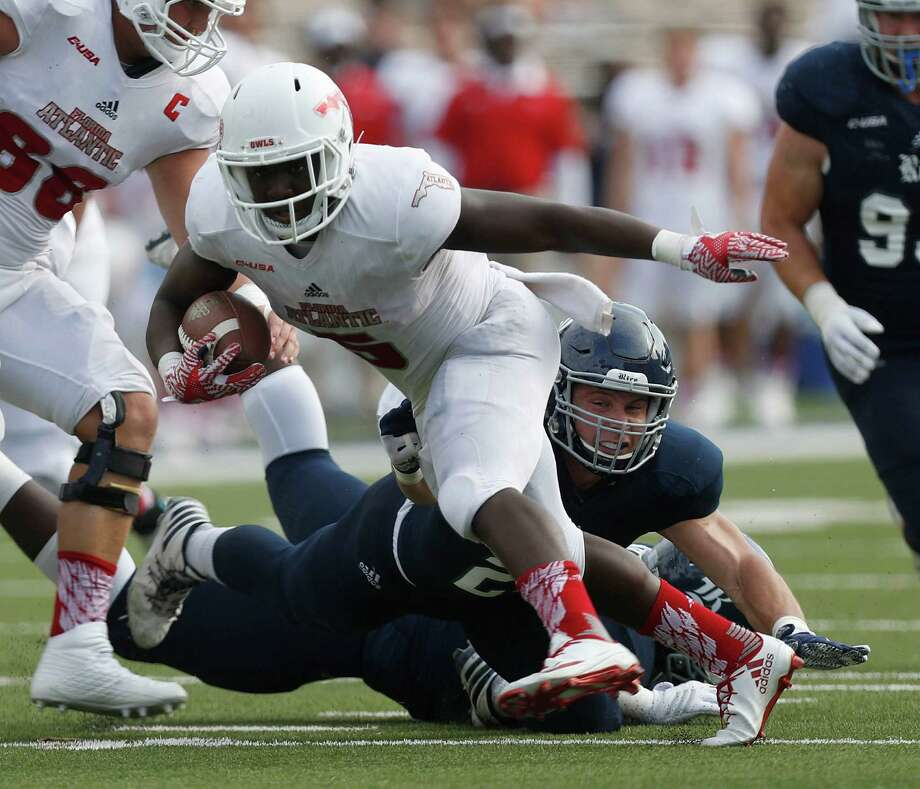 Florida Atlantic Owls running back Devin Singletary (5) gains yardage as Rice Owls linebacker Nick Uretsky (21) tries to take him down during the second quarter of a college football game at Rice Stadium, Saturday,Nov. 5, 2016 in Houston. Photo: Karen Warren, Houston Chronicle / 2016 Houston Chronicle