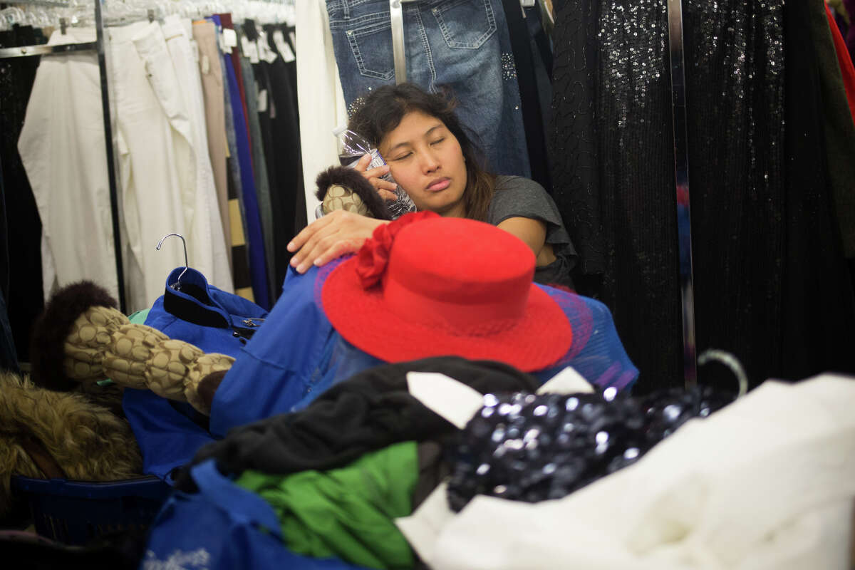 Jet Nilo rests in a pile of clothes her and her sister gathered at 33rd annual Goodwill Glitter Sale in Seattle on Saturday, Nov. 5, 2016. Nilo was #13 in line and had been waiting since Friday evening.