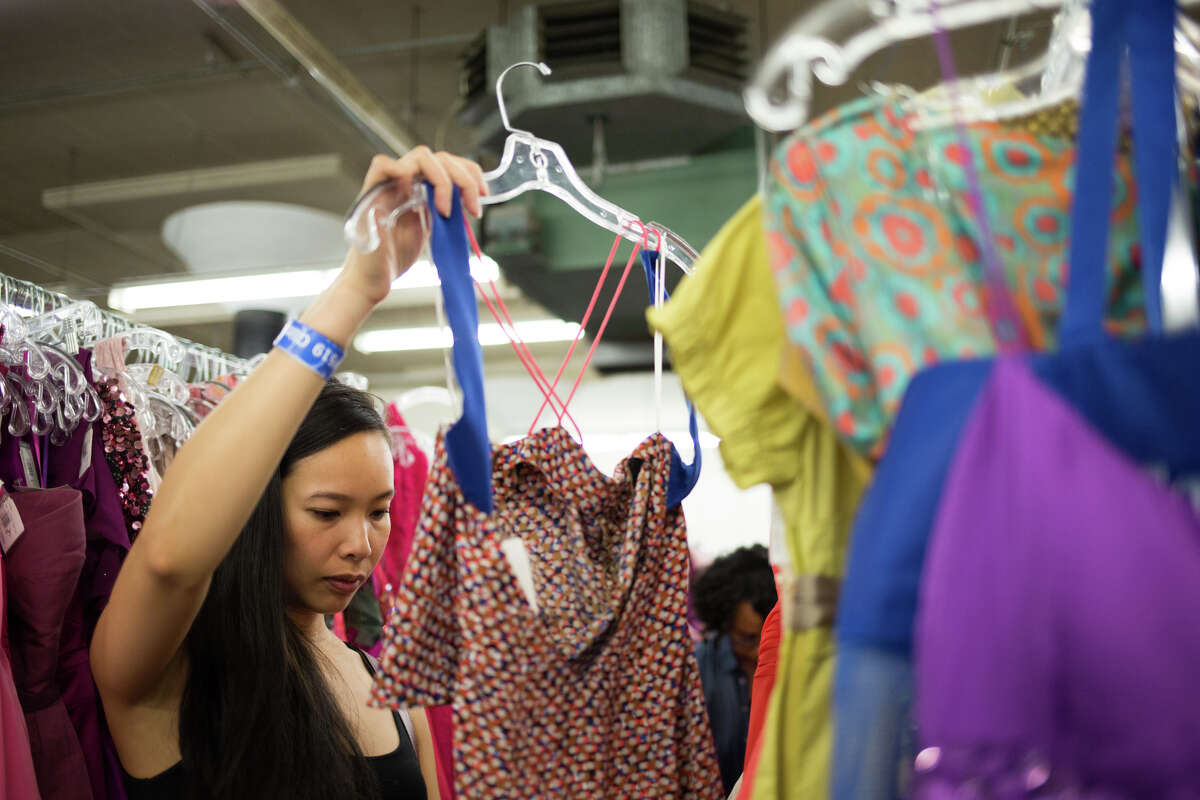 Thao Le looks through dresses at the 33rd annual Goodwill Glitter Sale in Seattle on Saturday, Nov. 5, 2016.