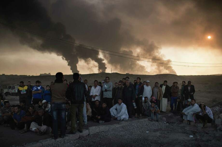 Men are held by Iraqi national security agents, to be interrogated at a checkpoint, as oil fields burn in Qayara, south of Mosul, Iraq, Saturday, Nov. 5, 2016. Islamic State fighters launch counterattacks in the thin strip of territory Iraqi special forces have recaptured in eastern Mosul, highlighting the challenges ahead as the battle moves into more densely populated neighborhoods where coalition air power must be used more selectively. (AP Photo/Felipe Dana) Photo: Felipe Dana, STF / Copyright 2016 The Associated Press. All rights reserved.