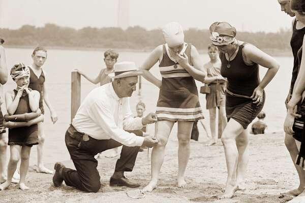 Woman having her swimsuit measured for length violations on a Washington DC beach in the 1920s.