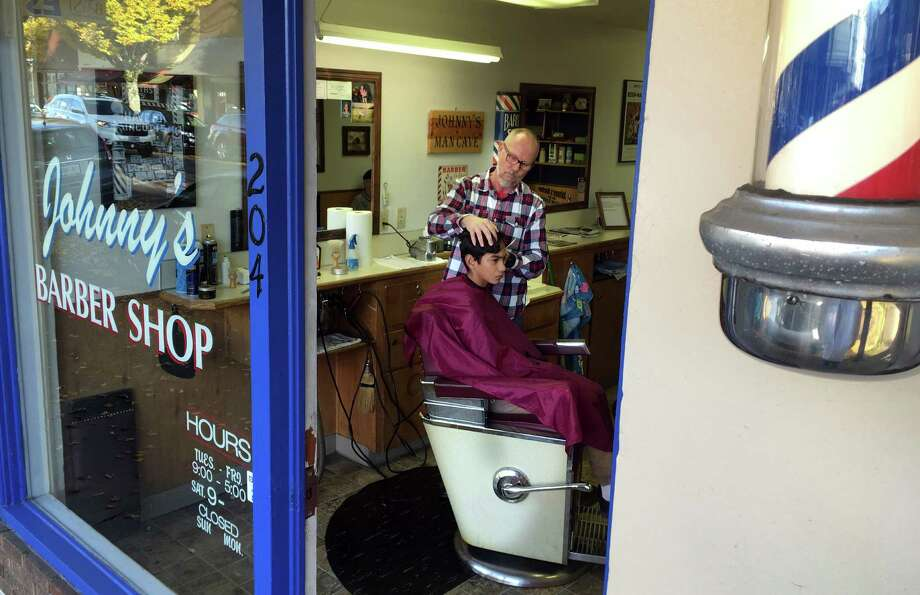 Johnny Moye attends to a young customer on Nov. 1, 2016 in his barbershop in Silverton, Oregon. The town of about 9,500 residents in eastern Oregon is almost evenly split between Republicans and Democrats, and they are pondering national, state and local elections. (AP Photo/Andrew Selsky) Photo: Andrew Selsky, STF / Copyright 2016 The Associated Press. All rights reserved.