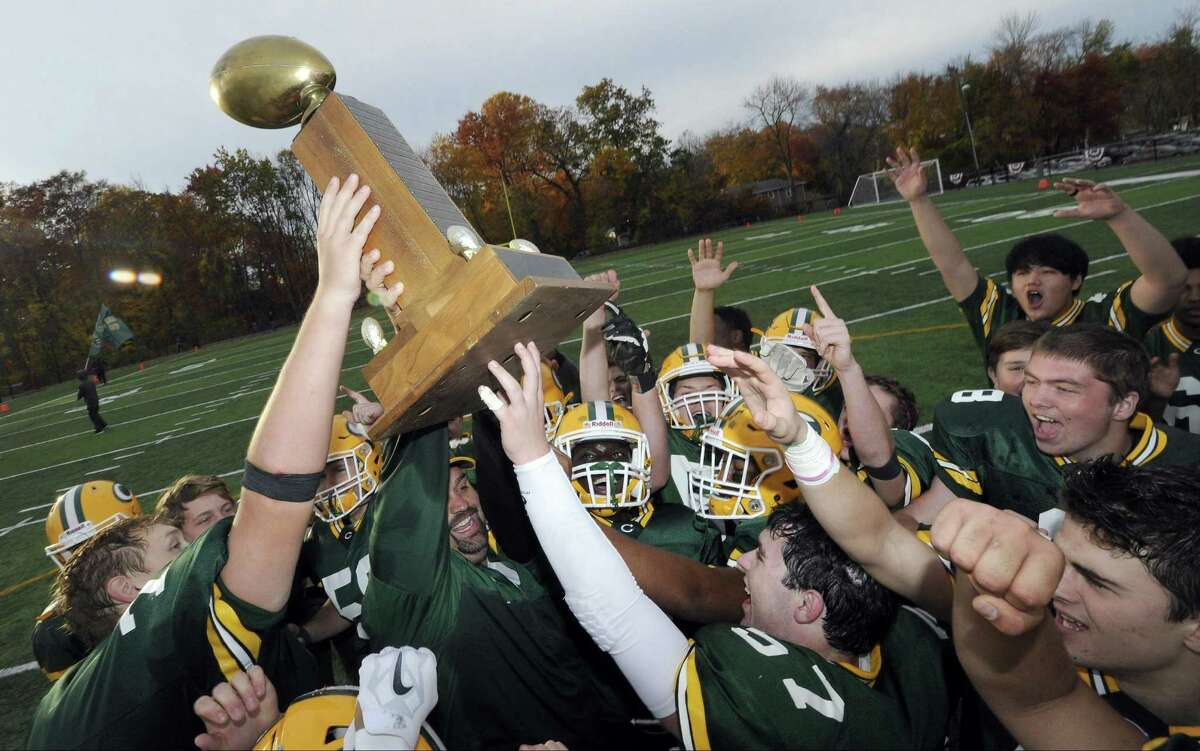 Trinity Catholic coach Donny Panapada celebrates winning the Stamford City Championship with his team following their 38-13 win over rival Stamford at Gaglio Field in Stamford, Conn on Sat., Nov. 5, 2016.