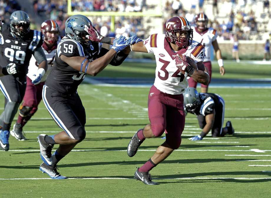 Duke's James Hornbuckle (59) chases Virginia Tech's Travon McMillian (34) as McMillian rushes for a touchdown during the first half of an NCAA college football game in Durham, N.C., Saturday, Nov. 5, 2016. (AP Photo/Gerry Broome) Photo: Gerry Broome, STF / Copyright 2016 The Associated Press. All rights reserved.
