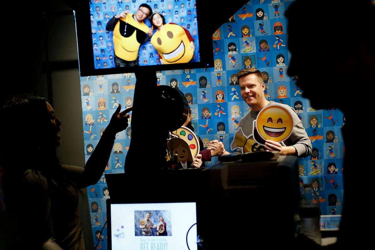 From left: Naomi Wardell takes a photo of Daniel Tate, who is holding a smiley-face emoji at the photobooth, during the first-ever Emojicon, at the Westfield San Francisco Centre, on Saturday, Nov. 5, 2016 in San Francisco, Calif.