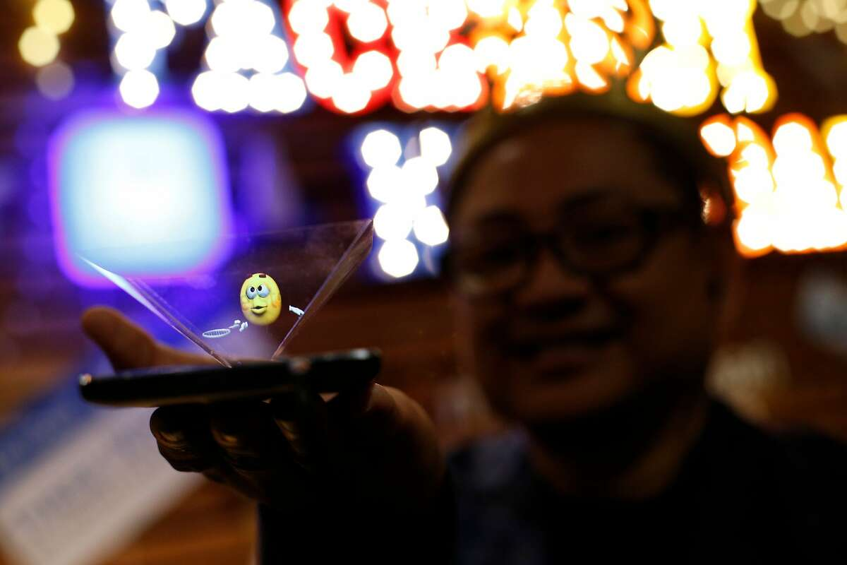 Ed Zapanta, the co-founder of Holospace X and inventor, demonstrates his emoji hologram invention, during the first-ever Emojicon, at the Westfield San Francisco Centre, on Saturday, Nov. 5, 2016 in San Francisco, Calif.