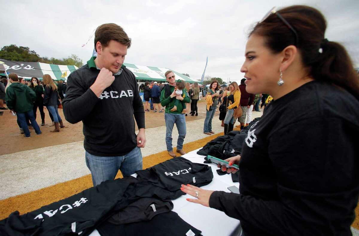 Baylor fan Jon McClellan of Houston purchases shirts Saturday in Waco from Celsa Hurley of Hurley's Graphics that have #CAB printed on them. The #CAB stands for Coach Art Briles.