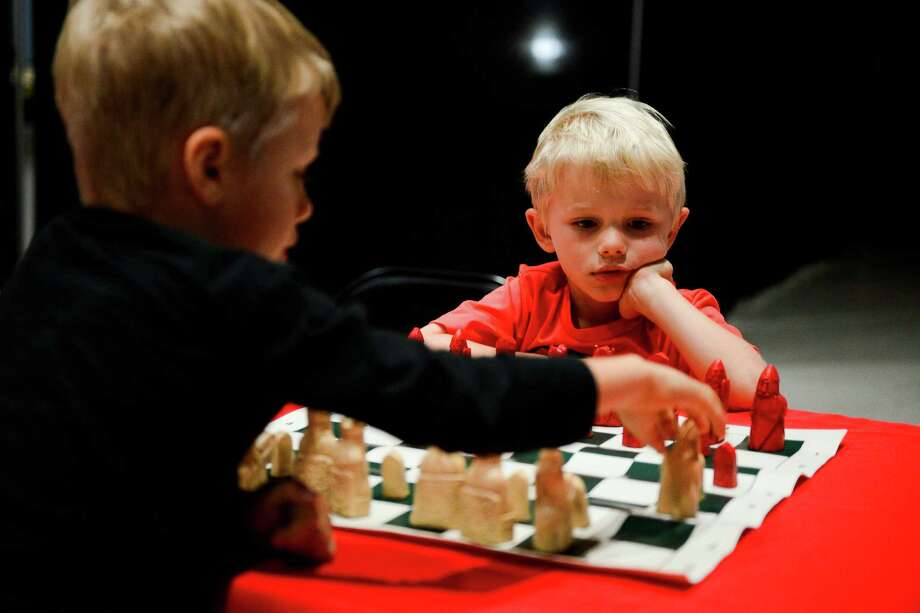 Baltazar and Hubert Kudlicki play chess together at the Houston Museum of Natural Science during the Ancient Games Festival on Saturday. Irving Finkel, the British Museum's curator, said games reveal how societies develop. Photo: Erin Hull, For The Washington Post / Erin Hull
