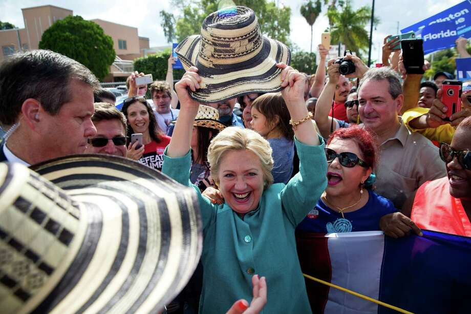 Hillary Clinton holds up a hat given to her during a surprise campaign stop at the city hall in West Miami, Fla., Nov. 5, 2016. (Doug Mills/The New York Times) ORG XMIT: XNYT41 Photo: DOUG MILLS / NYTNS