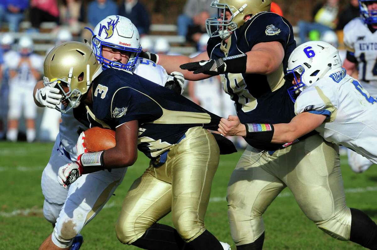 Notre Dame of Fairfield's Taevian Jackson is grabbed from behind by Newtown's Mark Hall and tackled by Tom Long during football action in Fairfield, Conn. on Saturday Nov. 5, 2016.