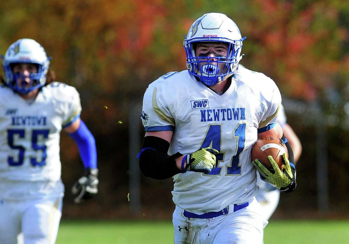 Newtown's Ben Mason carries the ball to the endzone to score after intercepting a Notre Dame of Fairfield pass during football action in Fairfield, Conn. on Saturday Nov. 5, 2016.