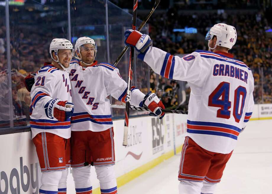 New York Rangers center Derek Stepan (21) is congratulated by teammates Dan Girardi, center, and Michael Grabner (40) after scoring a goal during the first period of an NHL hockey game against Boston Bruins, Saturday, Nov. 5, 2016, in Boston. (AP Photo/Mary Schwalm) ORG XMIT: MAMS102 Photo: Mary Schwalm / FR158029 AP
