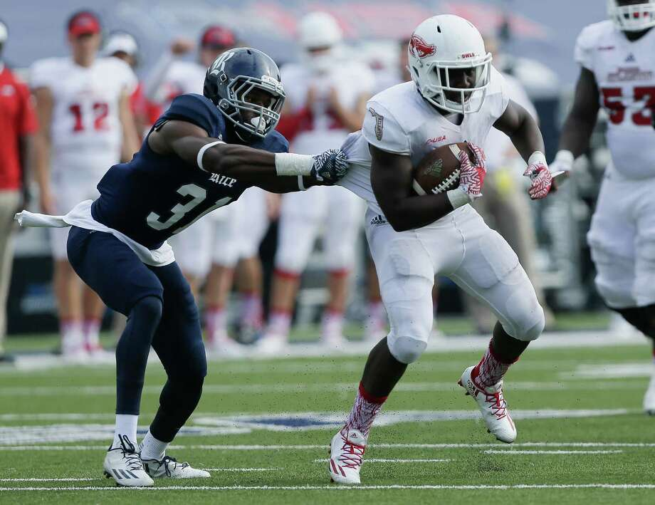 HOUSTON, TX - NOVEMBER 05:  Devin Singletary #5 of the Florida Atlantic Owls is grabbed by Martin Nwakamma #31 of the Rice Owls at Rice Stadium on November 5, 2016 in Houston, Texas.  (Photo by Bob Levey/Getty Images) Photo: Bob Levey, Stringer / 2016 Getty Images