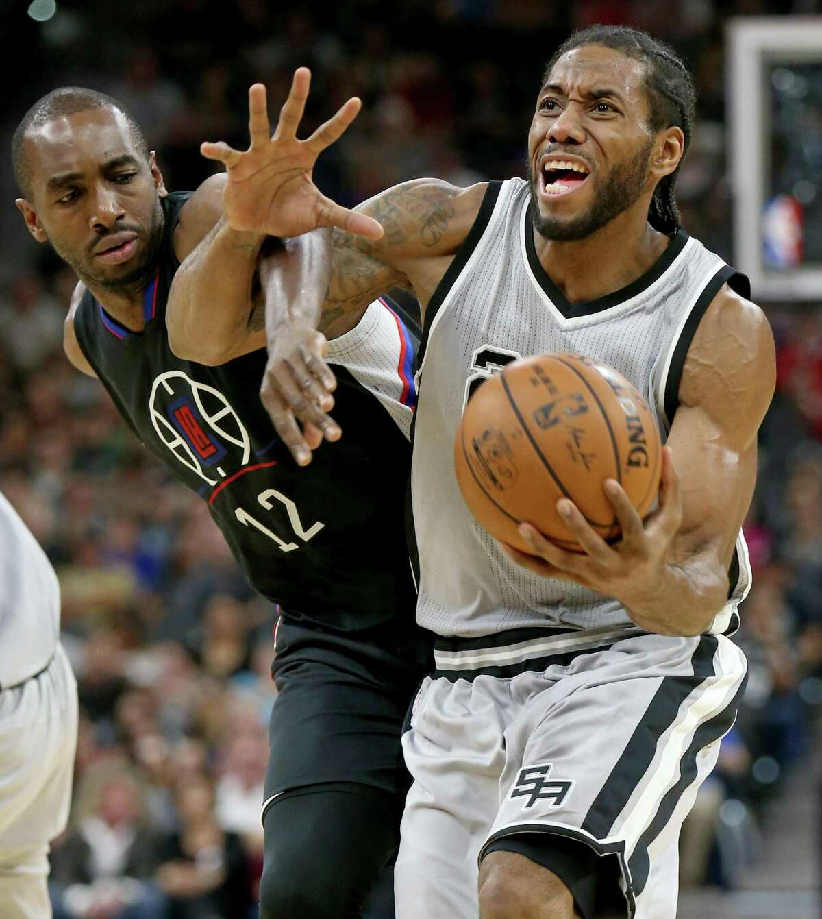 San Antonio Spurs' Kawhi Leonard is fouled by Los Angeles Clippers' Luc Richard Mbah a Moute during first half action Saturday Nov. 5, 2016 at the AT&T Center.