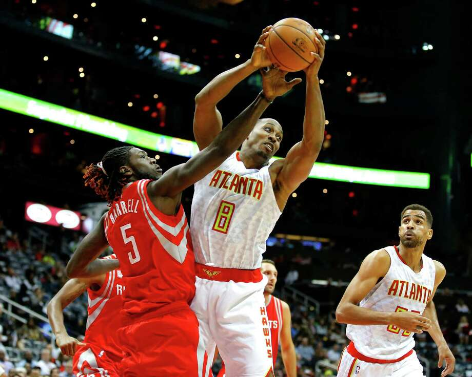 Hawks center Dwight Howard hauls in a rebound over Rockets forward and former teammate Montrezl Harrell, left, during Saturday's game. Howard had 20 points and 14 rebounds in the Hawks' 112-97 victory. Photo: Todd Kirkland, FRE / 2016