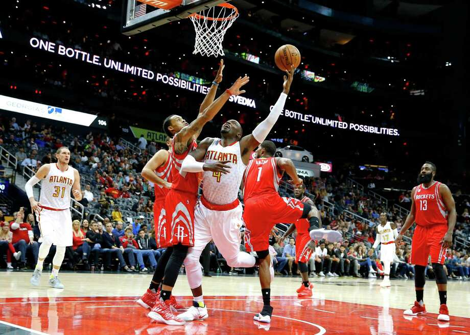 Hawks forward Paul Millsap, center, squeezes between a pair of Rockets defender in the first half to score two of his team-high 23 points Saturday night. Photo: Todd Kirkland, FRE / 2016