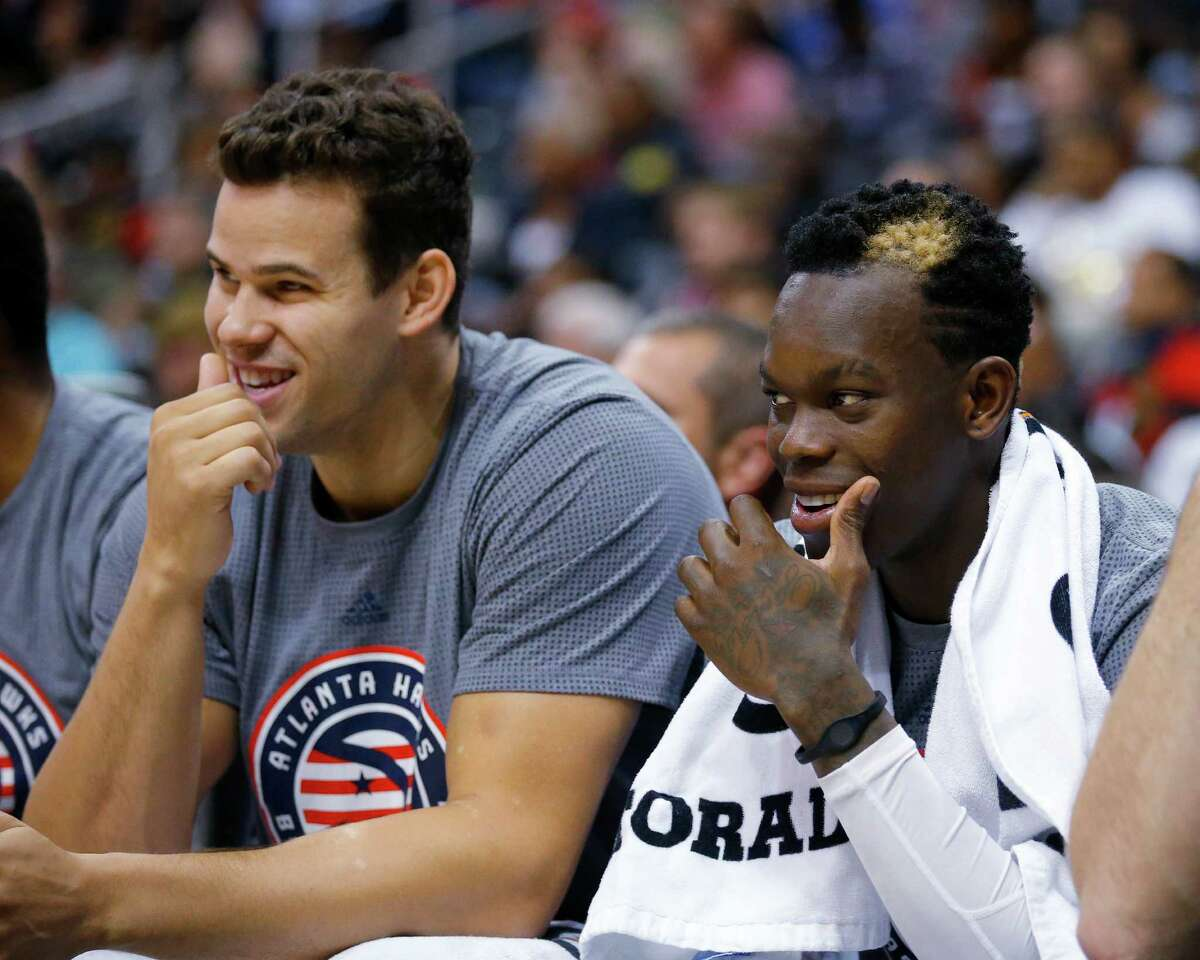 Atlanta Hawks guard Dennis Schroder, right, laughs with teammate Kris Humphries while watching during the second half of the team's NBA basketball game against the Houston Rockets on Saturday, Nov. 5, 2016, in Atlanta. The Hawks won 112-97. (AP Photo/Todd Kirkland)
