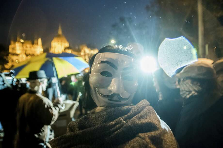 Participants of the Million Mask March event in central Budapest, Hungary, Saturday, Nov. 5, 2016.   The annual protest is one of many similar marches held worldwide on November 5, broadly aimed at anti-capitalism and pro-civil liberty. Photo: Zoltan Balogh/AP