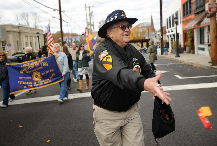 Vietnam veteran Don LaReau, of Stratford, tosses candy to children as he marches in the annual Veterans Day parade on River Street in Milford, Conn. on Sunday, November 6, 2016. Photo: Brian A. Pounds / Hearst Connecticut Media / Connecticut Post