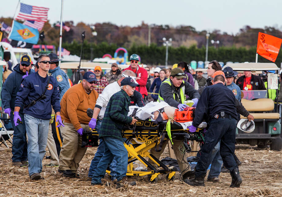 Paramedics rush a man to an ambulance after he and a woman were injured when an air cannon used to launch pumpkins into the air exploded Sunday. Photo: Kyle Grantham, MBO / The Wilmington News-Journal