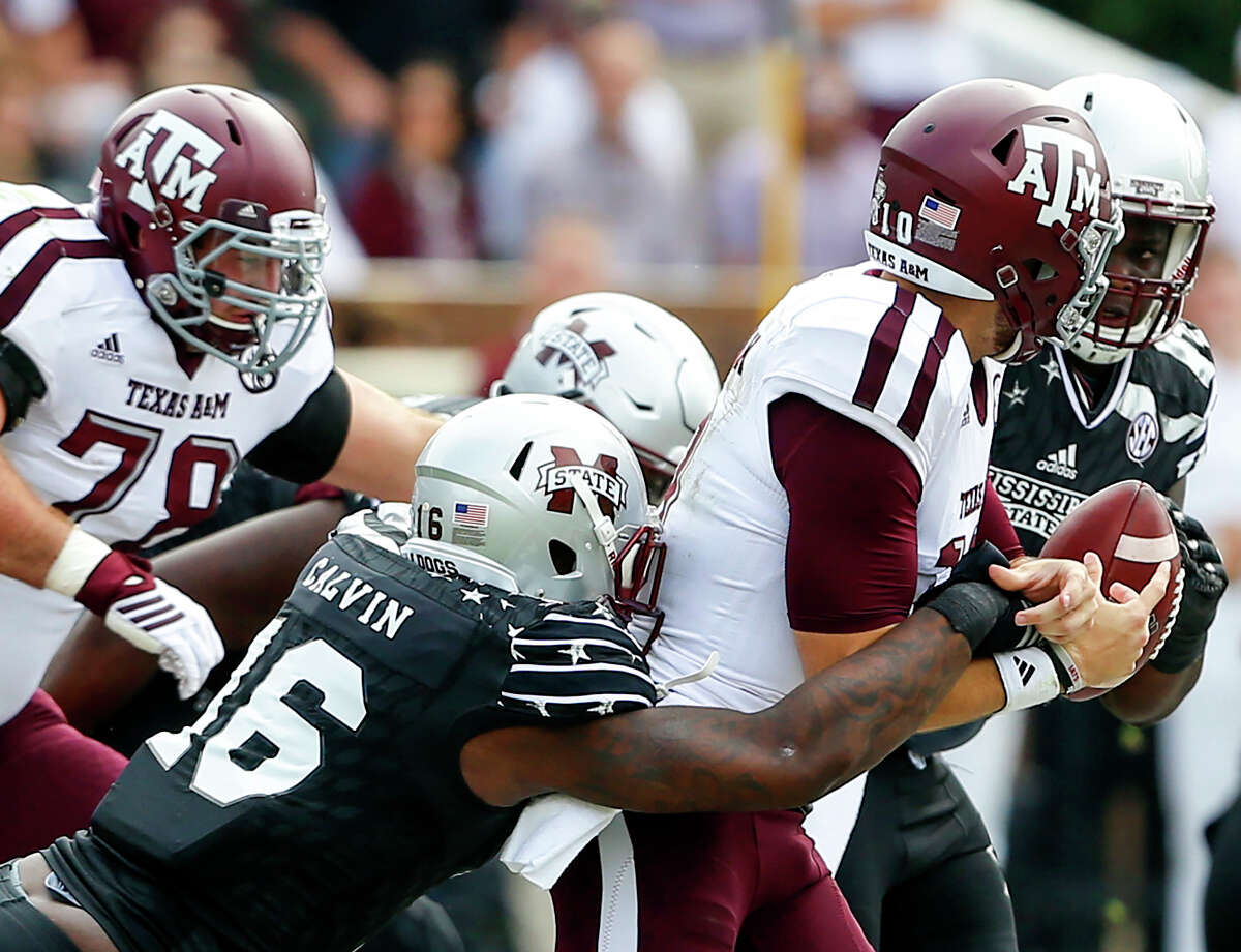 Mississippi State defensive lineman Johnathan Calvin, left, strips the ball from Texas A&M quarterback Jake Hubenak, and the Bulldogs recovered the fumble.