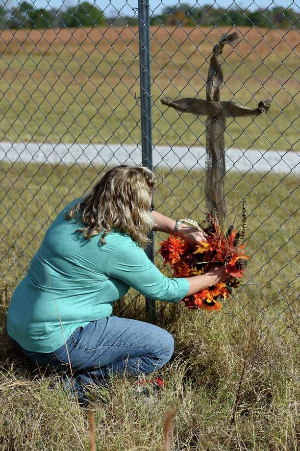 JoAnn McKinney, a local resident, prepares a cross on the fence of Todd Kohlhepp's property in Woodruff, S.C. Sunday, Nov. 6, 2016. Authorities have charged Kohlhepp, 45, with four counts of murder in the deaths of four people in 2003 at the Superbike Motorsports motorcycle shop. His alleged role in those killings was uncovered, authorities said, after the woman was found last week in a locked metal container on Kohlhepp's property in rural Woodruff.  (AP Photo/Richard Shiro) ORG XMIT: SCRS122 Photo: Richard Shiro / FR159523 AP