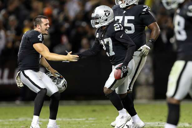 Oakland Raiders'Derek Carr congratulates Reggie Nelson after Nelson's 4th quarter interception clinched Raiders' 30-20 win over Denver Broncos in NFL game at Oakland Coliseum in Oakland, Calif., on Sunday, November 6, 2016.