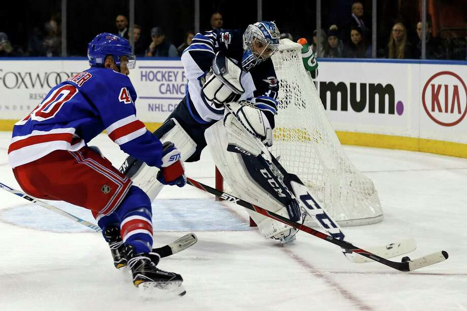 Winnipeg Jets goalie Michael Hutchinson (34) knocks the puck away from New York Rangers right wing Michael Grabner (40) in the second period of an NHL hockey game, Sunday, Nov. 6, 2016, in New York. (AP Photo/Adam Hunger) ORG XMIT: MSG104 Photo: Adam Hunger / FR110666 AP