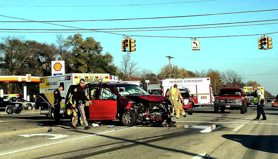 Sheriff's deputies and fire and rescue personnel work the scene of a three-vehicle accident at the intersection of M-20 and Meridian Road on Saturday.