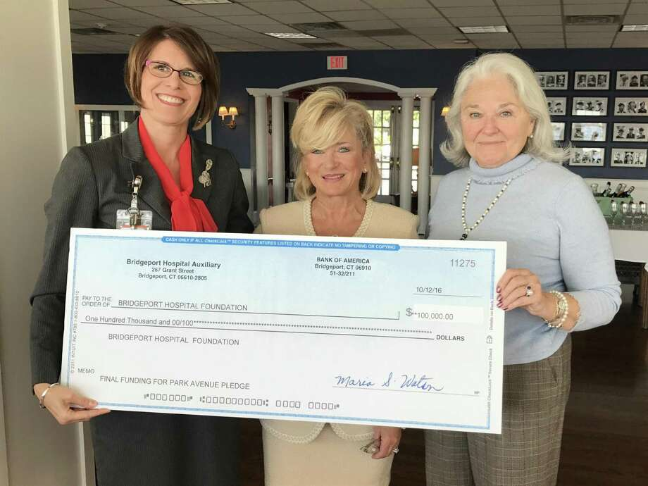 Bridgeport Hospital Chief Operating Officer Pamela Scagliarini (left) accepts the final $100,000 installment of the Bridgeport Hospital Auxiliary's $450,000 pledge toward the ambulatory surgery waiting room at Park Avenue Medical Center from Auxiliary President Bonnie Molloy (center) and Vice President Anne Pappas Phillips (right). Auxiliary proceeds during the current fiscal year will support the hospital's Newborn ICU and outpatient rehabilitation medicine programs.   Photo courtesy of Bridgeport Hospital. Photo: Contributed / Contributed