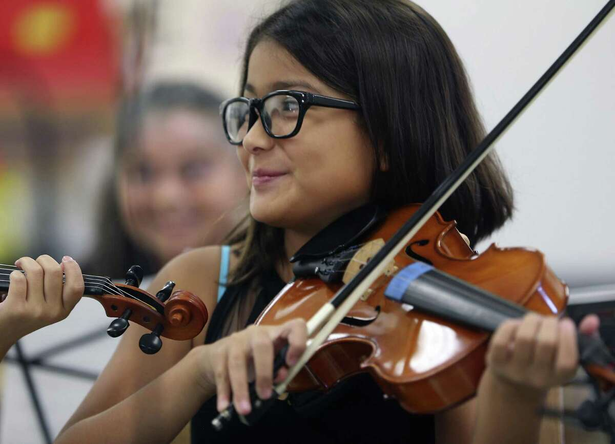 Winston Elementary school student Anisa Rivera smiles at a fellow violin player Wednesday afternoon, Nov. 2, 2016 as she and several classmates play during a brief event to thank the Youth Orchestra of San Antonio for their donation of instruments to Winston.