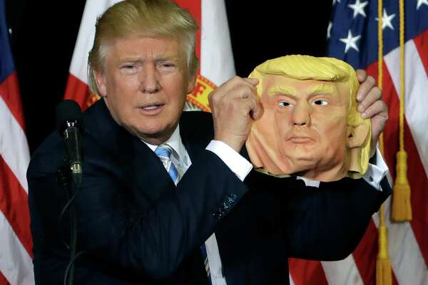 Republican presidential candidate Donald Trump holds up a Donald Trump mask during a campaign speech, Monday, Nov. 7, 2016, in Sarasota, Fla.
