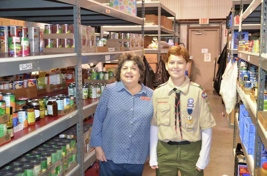 On Dec. 5, Boy Scout Troop 468 went door-to-door and collected approximately 1,400 pounds of dry goods for Christian Helping Hands.  Star Scout Vaughn Gaussiran led the service project. Here is Gaussiran with Robbie McDonald of Christian Helping Hands. Photo: Boy Scout Troop 468