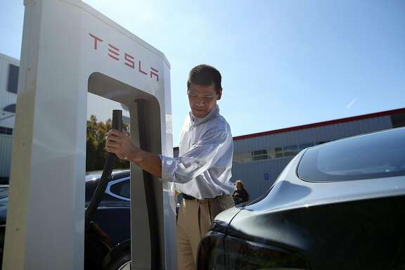 FREMONT, CA - AUGUST 16:  Frank Chou prepares to plug the Tesla Supercharger into his Tesla Model S sedan outside of the Tesla Factory on August 16, 2013 in Fremont, California. Tesla Motors opened a new Supercharger station with four stalls for public use at their factory in Fremont, California. The Superchargers allow owners of the Tesla Model S to charge their vehicles in 20 to 30 minutes for free. There are now 18 charging stations in the U.S. with plans to open more in the near future.  (Photo by Justin Sullivan/Getty Images)