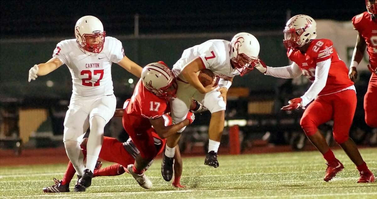 Judson defenders Chris Mills (17) and Kevin Wood (28) bring down New Braunfels Canyon quarterback Javier Perez during Judson's 17-9 win Friday at Rutledge Stadium.